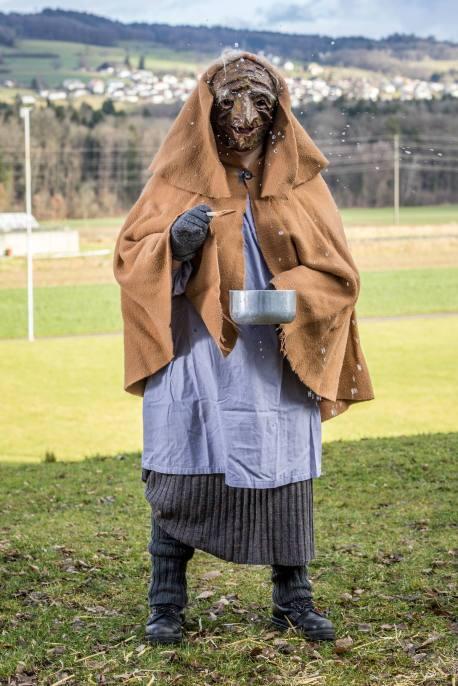 HALLWIL/AG 02. JANUAR 2018 - SERIE SEHTAL.COM BLOG: PATRICK SENN als LOERTSCH (alte Frau), die aus einer Pfanne ein fruchtbares Waesserchen verspritzt, Symbol fuer Haesslichkeit, Alter und Laster. Brauchtum im Seetal: Baerzeli-Buebe am Berchtoldstag (Baerzelistag). 15 maskierte junge Maenner huellen sich am Nachmittag des Baerzeli-Tags (2. Januar) in ihre imposanten Kostueme: Staechpaumig, Tannreesig, Straumaa und Hobuspoeoenig haben aufwendige tagelange Vorarbeiten hinter sich. Fotos zu Projekt Sehtal (Luzerner Seetal). ths/Photo by: THOMI STUDHALTER, PHOTOS&MORE, www.studhalter.org