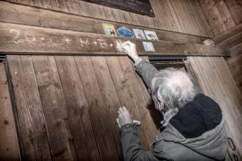 Beat Lustenberger schreibt mit geweihter Kreide die traditionelle Segensbitte C+M+B mit der jeweiligen Jahreszahl an die Haustüren oder die Türbalken
