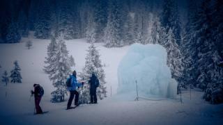 Schneewanderer vor imposanter Eisskulptur im tiefverschneiten Kaltbad.